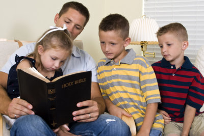 A father reads to his three young children from the Holy Bible